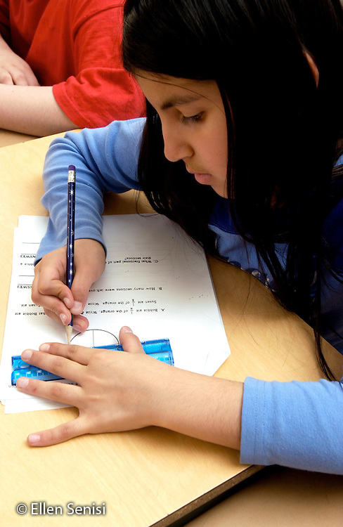 "MR / Schenectady, NY.Yates Arts-in-Education Magnet School (urban elementary school) .Grade 4.Girl (9, Puerto-Rican American) uses ruler to do practice test for upcoming statewide standardized exam in math, one of three Elementary Level State Assessments they will take in fourth grade. Scores are critical for New York State schools, as results of State Assessments are used to prepare report cards on the effectiveness of individual schools and of school districts. A ""failing"" school can be put on probation and, if it does not improve, have its state aid taken away. Exams are graded 1 through 4; 1 is a failing grade, 2 indicates the student is ""at risk "". Unfunded mandate requires schools to provide AIS (Academic Intervention Services) to ""at-risk""  students..MR: Col8.©Ellen B. Senisi"