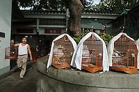 Market vendor selling caged birds, Kowloon, Hong Kong, China.