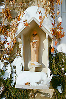 Bird feeder with statue of St. Francis holding two doves and surrounded by orange bittersweet berries in winter snow