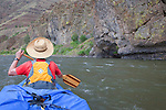 Robbie Scott in the bow of a canoe with spray cover.  John Day River, Oregon.Cliff is basalt, a volcanic rock.