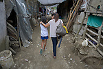 Raquel Fabre, a teacher with the Kapatiran-Kaunlaran Foundation (KKFI), walks with a girl in Pulilan, a village in Bulacan, Philippines.<br /> <br /> KKFI is supported by United Methodist Women.