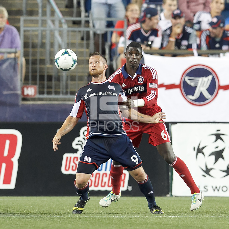 New England Revolution forward Chad Barrett (9) attempts to control the ball as Chicago Fire defender Jalil Anibaba (6) pressurs. In a Major League Soccer (MLS) match, the New England Revolution (blue) defeated Chicago Fire (red), 2-0, at Gillette Stadium on August 17, 2013.