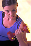 woman lifting dumbbells during workout in health club