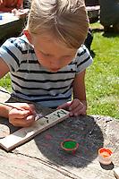 Grundschulklasse, Schulklasse im Schulgarten an ihrem selbst angelegtem Schulteich, Schul-Teich, Gartenteich, Garten-Teich, Kinder, Mädchen malen Schilder mit den Namen der Pflanzen am Teich, Exkursion am Teich, Biologie-Unterricht im Freien, Grünes Klassenzimmer
