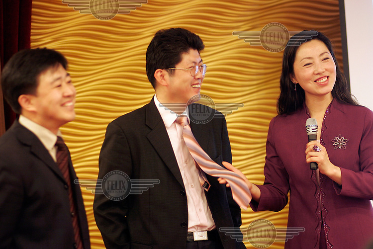 Teacher Liu Wei demonstrates the difference between formal and informal neck ties during a promotional lesson in social and corporate etiquette..