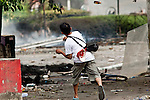 18 MAY 2010 - BANGKOK, THAILAND: A man throws a home made petrol bomb towards army lines at Din Daeng Intersection in Bangkok Tuesday. The intersection has been under periodic sniper fire from unidentified snipers near Thai military lines. Violent unrest continued in Bangkok again Tuesday nearly a week after Thai troops started firing on protesters and Bangkok residents took to the streets in violent protest against the government. Tuesday was not as violent as previous days however. Although protesters continued to set up roadblocks and flaming tire barricades across parts of the city, there was not as much gunfire from the government lines. The most active protesters were at the Din Daeng Intersection about a mile from the Red Shirts' Ratchaprasong camp.  PHOTO BY JACK KURTZ