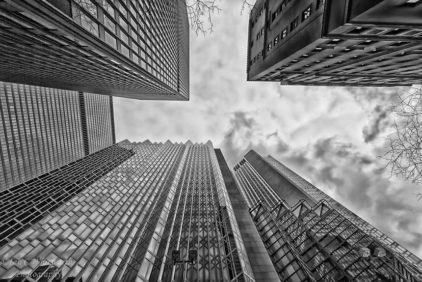 A black and white view looking up between the skyscrapers in downtown Toronto's financial district.