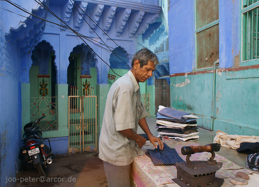 man ironing clothes in the streets of Jodhpur,  Rajastan, India