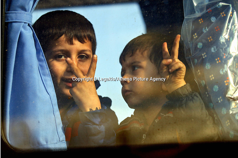 Pictured: Two young boys give the victory sign from a coach that transferred them to a local gymnasium Thursday 27 November 2014<br />