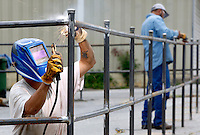 NWA Democrat-Gazette/DAVID GOTTSCHALK  Brandon Baker, with Center Point Contractors Inc. of Bentonville, uses arc welding to join steel bars for a fenced in area Thursday, August 27, 2015 in Fayetteville. Arc welding uses a welding power supply to create an electric arc between an electrode and the base material to melt the metals at the welding point.