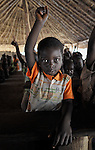 A child raises his hand in a Catholic Church-sponsored school in the Makpandu refugee camp in Southern Sudan, 44 km north of Yambio, where more that 4,000 people took refuge in late 2008 when the Lord's Resistance Army attacked their communities inside the Democratic Republic of the Congo. Attacks by the LRA inside Southern Sudan and in the neighboring DRC and Central African Republic have displaced tens of thousands of people, and many worry the attacks will increase as the government in Khartoum uses the LRA to destabilize Southern Sudan, where people are scheduled to vote on independence in January 2011. Catholic pastoral workers have accompanied the people of this camp from the beginning. NOTE: In July 2011 Southern Sudan became the independent country of South Sudan.