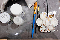 """Gouache paints lay on a work table next to a marble bust of abolitionist John Brown while conservators work on a replacement nose and eyebrow in the Tisch Family Gallery at the Tufts University Art Gallery at Tufts University in Medford, Massachusetts, on Thurs., Oct. 6, 2016. The bust was sculpted by Edward Augustus Brackett and had been improperly stored for decades with a broken nose and eyebrow. The conservators, from Rika Smith McNally and Associates, found a plaster cast made from the original at the Boston Athenæum and had a 3D modeler image the broken section of the original and the cast. They then used 3D printing technology to use to create a plaster nose replacement that would fit perfectly on the broken marble bust. They then used gouache paint to match the replacement pieces to the original marble.  The bust is part of an exhibition at the gallery entitled """"Mortal Things: Portraits Look Back and Forth."""""""