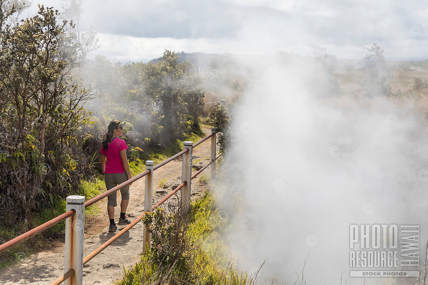 A woman walks past steam vents at Hawai'i Volcanoes National Park, Big Island.