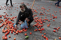 Pictured: A man collects tomatoes from the road after having been thrown by protesters to the police Friday 12 February 2016<br />Re: Violent clashes between farmers and riot police outside the Ministry of Agricultural Development in Athens, Greece. The farmers travelled from Crete to protest against pension and welfrae reforms proposed by the Greek government,