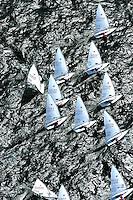 """Kieler Woche:EUROPA, DEUTSCHLAND, SCHLESWIG- HOLSTEIN 22.06.2005:Kieler Woche, Segler der Laser Klasse im Gedraenge beim Regattastart...Der Laser ist eine 4,23 m lange, 1,37 m breite und 57 kg (Rumpf) schwere Einmann-Jolle mit einem Segel...Der Laser wurde 1970 vom Amerikaner Bruce Kirby als Einhand-Jolle entworfen. Primaere Zielsetzung war damals ein Boot für die Freizeit zu entwerfen, deshalb auch der ursprüngliche Name """"Freetime""""..Seine einfache Bauweise und niedrige Anschaffungskosten führten zu einer raschen Ausbreitung. Ende des Jahres 2004 gab es ca. 180.000 Boote auf der Welt!.Der Laser ist eine One-Design Bootsklasse und wird von der Firma Performance Sailcraft Ltd. in England gefertigt. Weiterhin gibt es Lizenznehmer in Australien und in Chile..Das Niveau in der Laser-Klasse gilt als eines der höchsten der olympischen Bootsklassen..Luftaufnahme, Luftbild,  Luftansicht."""