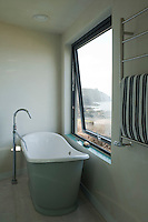 The free-standing bath is positioned by a large window which frames an open view of the beach and the sea