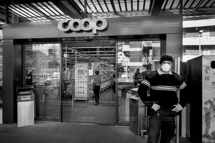 """Switzerland. Canton Ticino. Lugano. Supermarket Coop. A security guard working for the private company Securitas stands at the entrance of Coop Supermarket. The man wears a mask on the face and gloves on his hands to protect himself from the Coronavirus (also called Covid-19). His job is to control the door and and let enter only a restricted number of customers. Due to the spread of the coronavirus, the Federal Council has categorised the situation in the country as """"extraordinary"""". It has issued a recommendation to all citizens to stay at home, especially the sick and the elderly. The Federal Council (German: Bundesrat, French: Conseil fédéral, Italian: Consiglio federale, Romansh: Cussegl federal) is the seven-member executive council that constitutes the federal government of the Swiss Confederation. From March 16 the government ramped up its response to the widening pandemic, ordering the closure of bars, restaurants, sports facilities and cultural spaces. Only businesses providing essential goods to the population – such as grocery stores, bakeries and pharmacies – are to remain open. The Swiss Securitas Group stands for the optimal combination of technical security and safety solutions and services. It is the best partner for companies wishing to make everyday life safer. Coop is one of Switzerland's largest retail and wholesale companies. It is structured in the form of a cooperative society with around 2.5 million members. 18.03.2020 © 2020 Didier Ruef"""