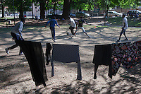 Italy. Lombardy Region. Como. Homeless african migrants living in the park below the San Giovanni railway station. Football game and clean laudry dying on a rope in the sun. 11.08.2016 © 2016 Didier Ruef