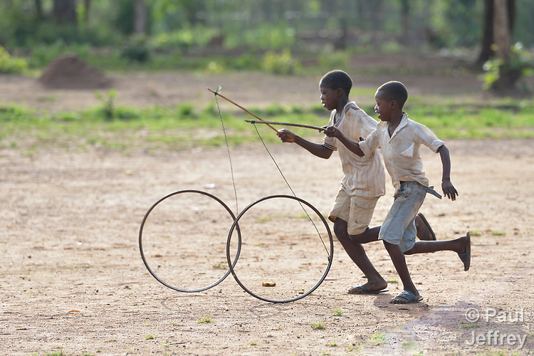 Boys roll bicycle wheels through a camp for more than 5,000 displaced people in Riimenze, in South Sudan's Gbudwe State, what was formerly Western Equatoria. Families here were displaced at the beginning of 2017, as fighting between government soldiers and rebels escalated.<br />