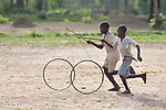 Boys roll bicycle wheels through a camp for more than 5,000 displaced people in Riimenze, in South Sudan's Gbudwe State, what was formerly Western Equatoria. Families here were displaced at the beginning of 2017, as fighting between government soldiers and rebels escalated.<br /> <br /> Two Catholic groups, Caritas Austria and Solidarity with South Sudan, have played key roles in assuring that the displaced families here have food, shelter and water.<br /> The camp formed around the Catholic Church in Riimenze as people fled violence in nearby villages for what they perceived as the safety offered by the church.