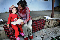 Stela Babus reads to her four year old daughter outside their home in rural Gagauzia an autonomous region of Moldova.
