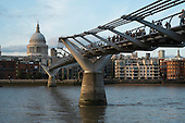 Pedestrians cross the Millenium Bridge across the River Thames, London.