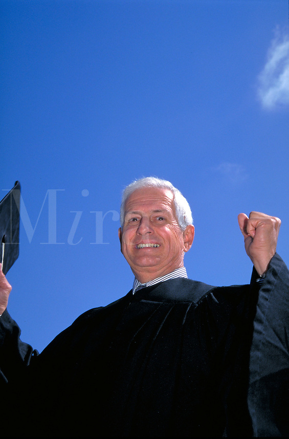 Senior Graduate in graduation gown, holding mortarboard cap, smiling, hands clenched in victory, achievement, accomplishment, education. Don Borie.
