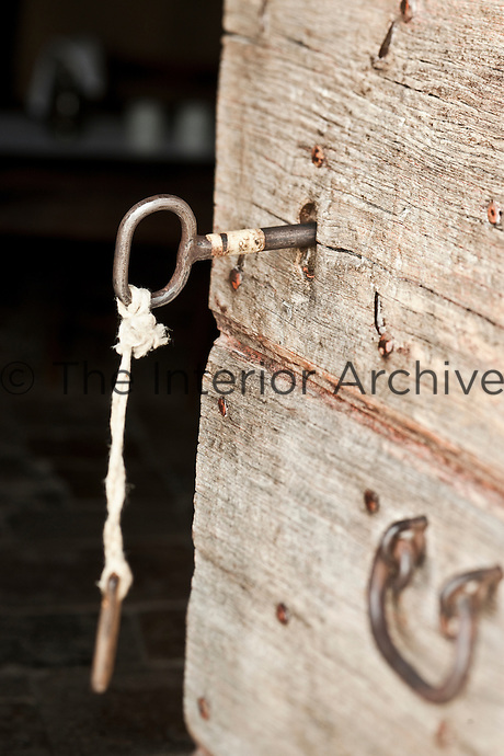 Close up of an old key in a wooden door at the Albergo Diffuso Le Grotte della Civita built within ancient caves in the town of Matera in Southern Italy