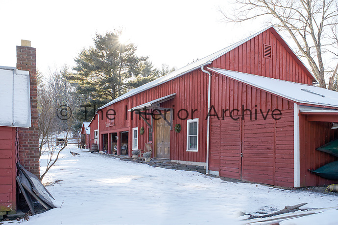 The red-painted clapboard barn stands out against the snow