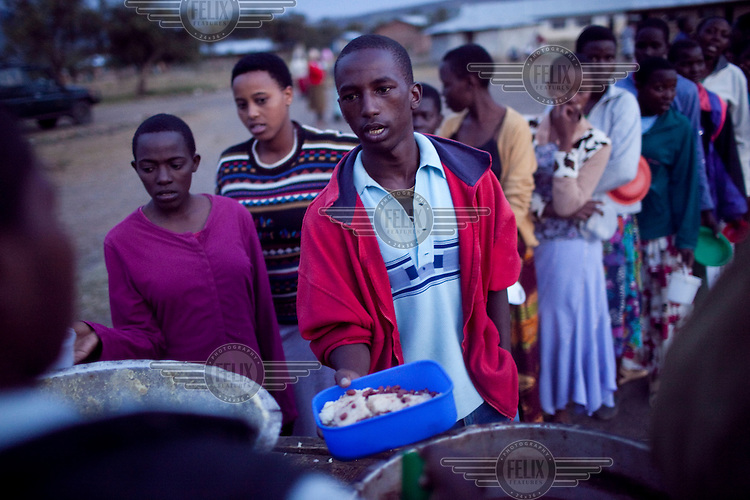 Students receive their dinner consisting of beans with a soft dough made from maize at the Noonkondin Secondary School run by Gemma Enolengila and Lesikar Olengila.