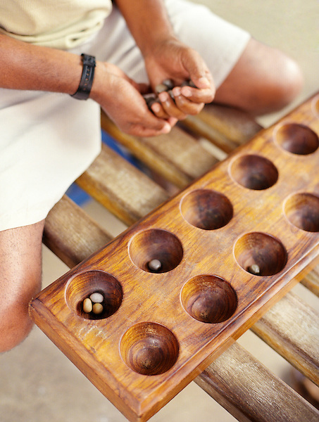 """Local men play ouril int the city of Mindelo. Cape Verde, Africa...Ouril is an abstract strategy game and is the variant of mancala most widely considered suitable for serious adult competition. Oware is the national game of Ghana, and the particular name """""""" is that given by the Akan speaking people there. It is played throughout West Africa and the Caribbean. Among its many names are Ayò (Yoruba), Awalé (Côte d'Ivoire), Wari (Mali), Ouri, Ouril or Uril (Cape Verde), Warri (Caribbean), Adji (Ewe), and Awélé (Ga). A common name in English is Awari but one of the earliest Western scholars to study the game, R.S. Rattray, used the name Wari...The object of mancala games is usually to capture more stones than the opponent; sometimes, one seeks to leave the opponent with no legal move or to have your side empty first in order to win."""