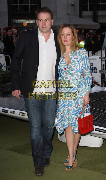 "MARK GRIFFITHS & GILLIAN ANDERSON.UK Premiere of ""The Age of Stupid"" held in a Solar Powered Tent in Leicester Square, London, England..March 15th, 2009.full length black suit jacket white shirt jeans denim blue green red pattern dress couple bag purse .CAP/ROS.©Steve Ross/Capital Pictures"