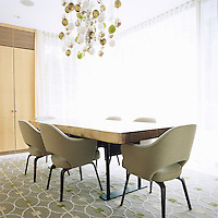 Eero Saarinen upholstered dining chairs surround a refectory dining table fashioned out of two large planks of wood