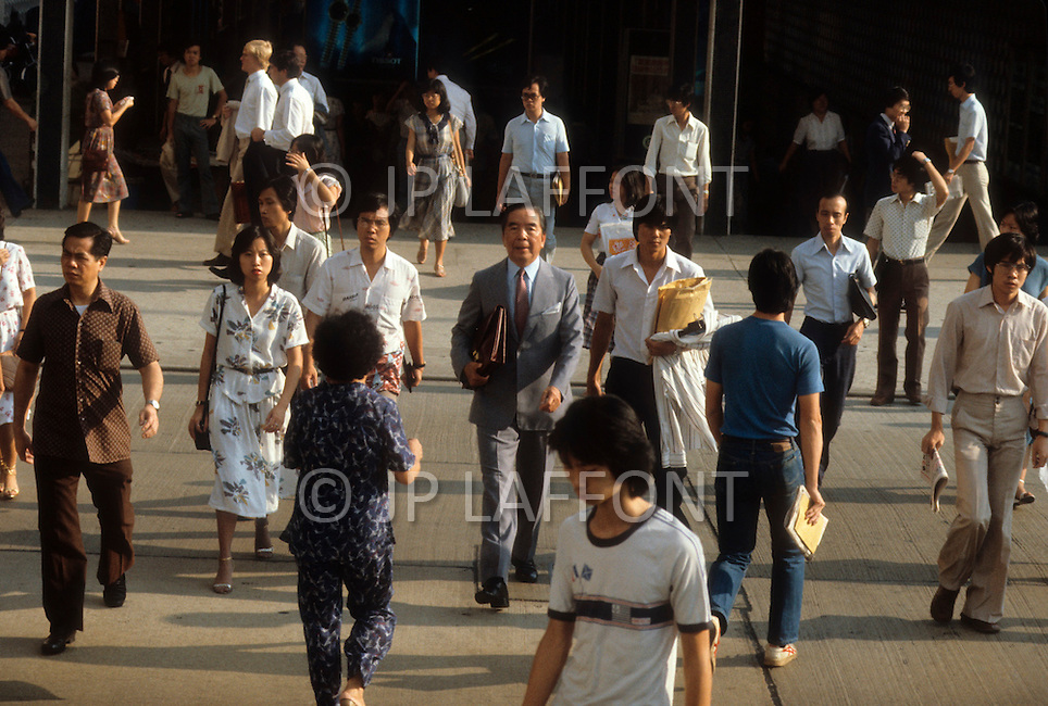 Hong Kong, China - September 25, 1981. Picture of Y.K. Pao taken walking through a crowded street of Hong Kong, wearing a suit and briefcase. Y.K. Pao (November 10, 1918 - September 23, 1991) was founder of the World-Wide Shipping Group that by the mid 1970's had become the largest shipping company in the world.