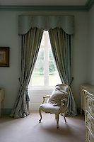 French chair beside tall bedroom window