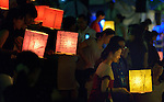 People carry floating candle lanterns to the river on August 6, 2015, in Hiroshima, Japan. The lanterns, thousands of which were launched on the 70th anniversary of the atomic bombing of the city, carried handmade messages and drawings, conveying each person's prayers for peace and comfort for the victims of the violence.
