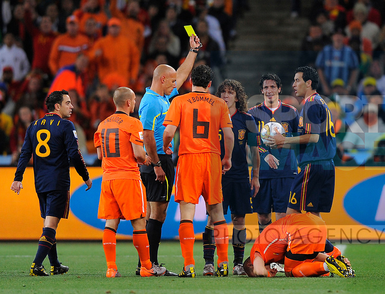 Referee Howard Webb issues a yellow card