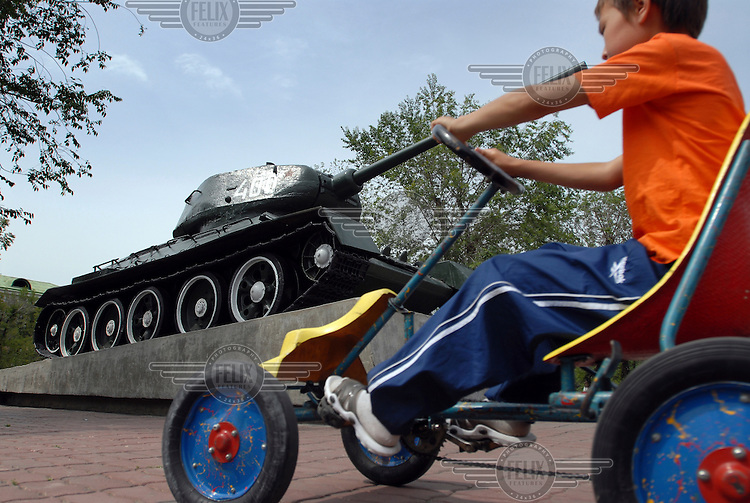 A boy drives a pedal car in a military park in Kyzyl.