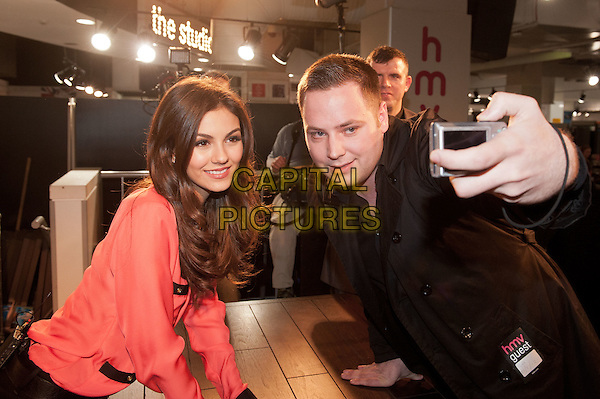 Victoria Justice.Fans of the hit Nickelodeon TV series VicTORious get the chance to meet the star, Victoria Justice, in person, when she visits HMV's flagship Oxford Street store in London's West End to sign copies of the VicTORious album, DVD & Game. .22nd February 2012.half length black table pink blouse fan taking picture photograph posing .CAP/HT.©Hugh Thompson/Capital Pictures.