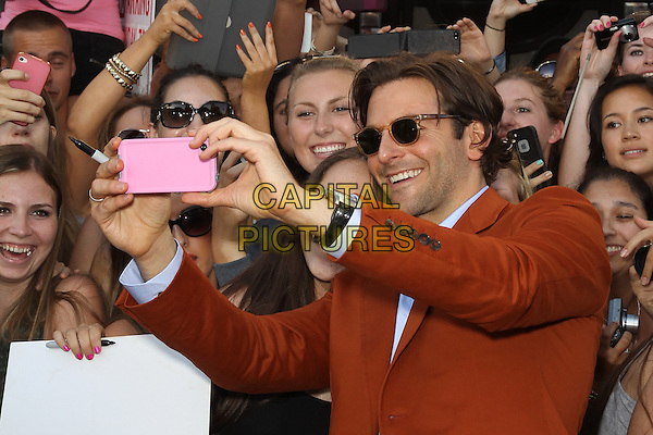 "Bradley Cooper.""The Hangover Part III"" Los Angeles Premiere held at the Westwood Village Theater, Los Angeles, California, USA..May 20th, 2013.half length sunglasses shades mobile camera fans crowd posing orange suit blue shirt taking picture photographs .CAP/CEL .©CelPh/Capital Pictures."