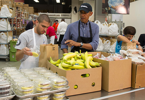 United States President Barack Obama helps pack food donation bags at Food &amp; Friends as part of the National Day of Remembrance and Service in Washington, D.C. on September 11, 2013. Obama volunteered his time on the 12th Anniversary of the terrorist attacks on 9/11.<br /> Credit: Kevin Dietsch / Pool via CNP