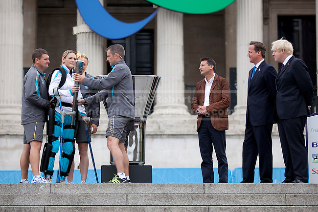 24/08/2012. LONDON, UK. Claire Lomas is watched by the Mayor of London, Boris Johnson (R), British Prime Minister, David Cameron (R2) and LOCOG Chairman Sebastian Coe (R3) as she prepares to light the Paralympic Cauldron in Trafalgar Square today (24/08/12). Ms Lomas, formerly a horse event rider, was paralysed from the chest down after being injured during the Osberton Horse Trials and, with the aid of her robotic suit, completed the London Marathon in 2012. Photo credit: Matt Cetti-Roberts