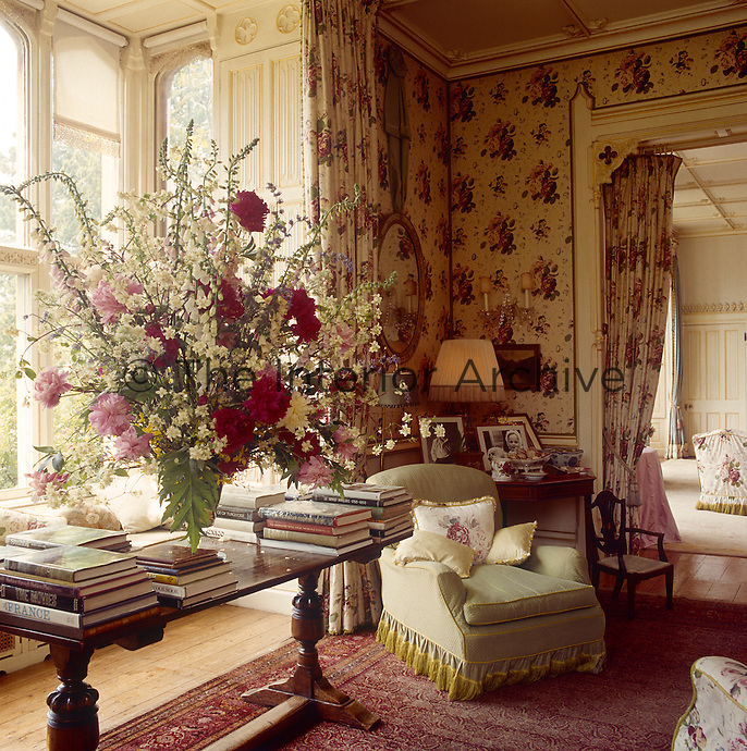 An arrangement of garden flowers in the living room echoes the pink and cream chintz used on the walls and soft furnishings