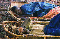 Rwandans Elizabeth Nyiramariro and Jean Paul Ndanguzi lie in basket-like litters awaiting care from medical personel of the AmeriCares clinic in Buranga, Rwanda, October 1994. The New Canaan Connecticut humanitarian organization set up their clinic on the road between Goma, Zaire (now Congo) and Kigali, Rwanda to help refugees returning from the camps in Goma and the people living in the area whose illnesses resulted from the destruction of what little infracstracture existed before civil war. (photo Rick D'Elia)