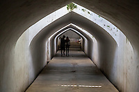 Yogyakarta, Java, Indonesia.  Young Couple Walking through Tunnel leading from the Underground Mosque, part of the Taman Sari (Water Palace) Complex.