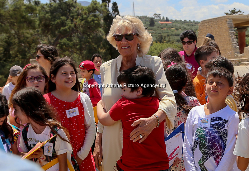 Pictured: The Duchess of Cornwall is embraceby a local child at Knossos on the island of Crete, Greece. Friday 11 May 2018 <br /> Re:HRH Prnce Charles and his wife the Duchess of Cornwall visit the ancient site of Knossos near Heraklion, Greece.
