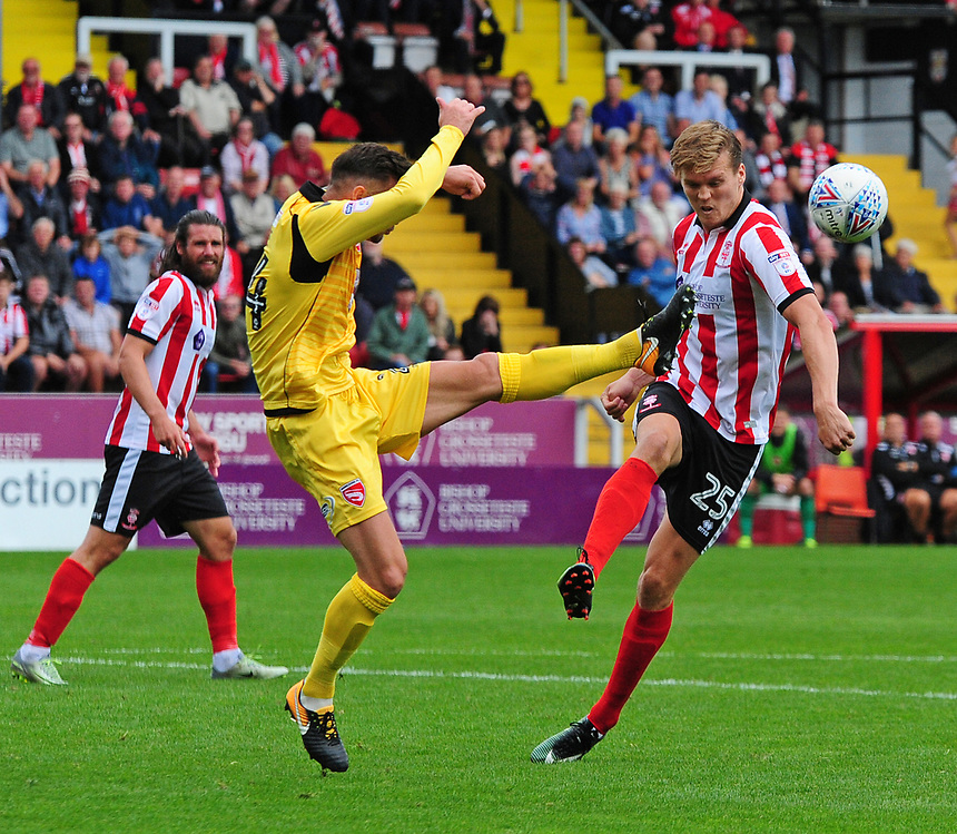 `Lincoln City's Sean Raggett vies for possession with Morecambe's Michael Rose<br /> <br /> Photographer Andrew Vaughan/CameraSport<br /> <br /> The EFL Sky Bet League Two - Lincoln City v Morecambe - Saturday August 12th 2017 - Sincil Bank - Lincoln<br /> <br /> World Copyright &copy; 2017 CameraSport. All rights reserved. 43 Linden Ave. Countesthorpe. Leicester. England. LE8 5PG - Tel: +44 (0) 116 277 4147 - admin@camerasport.com - www.camerasport.com