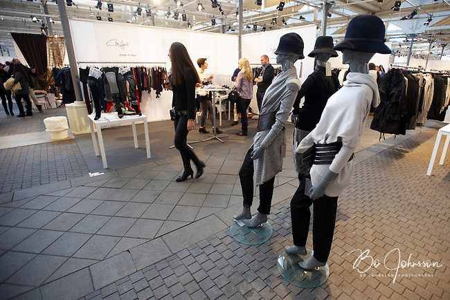 A visitor passing a gang of cool mannequins. Stylish hats and dresses designed by Annette Gortz, Denmark (www.nilleagentur.dk). Calzificio de Pio in the background.<br /> CPH Vision Fashion Fair in Oksnehallen during Copenhagen Fashion Week AW10, Denmark.<br /> February -10.<br /> Only for editorial use.