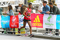 Abelhadi El Harti runs into 2nd place in the ambulant class during the 2017 Virgin Money London Marathon while exposing himself as a surprised spectator in the background realises while looking at her phone photos at London, England on 23 April 2017. Photo by Steve McCarthy/PRiME Media Images