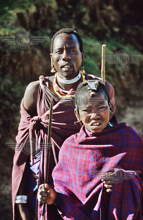 Maasai herders in traditional dress with earrings and necklaces in the Crater Highlands region, along the East African rift in Tanzania.